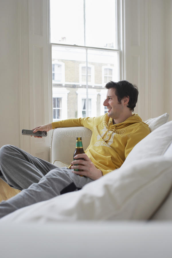 Man With Beer Bottle Watching TV On Sofa Stock Images