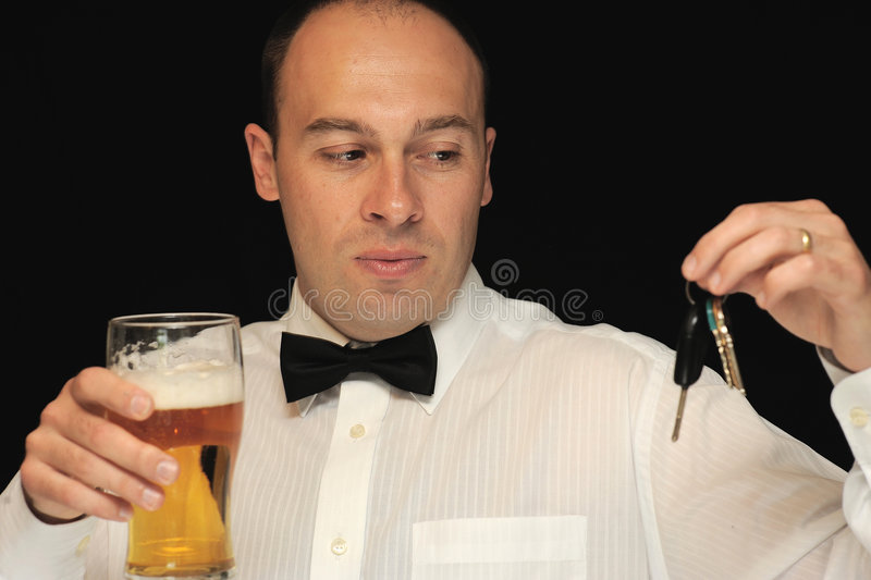 Man with beer and keys. A man holding a glass of beer and car keys royalty free stock photos