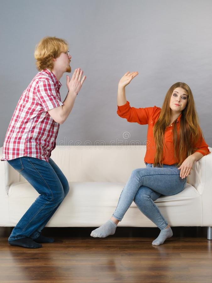 Man begging for forgiveness his woman. Man begging women who is sitting on sofa for forgiveness. Couple after fight or argue. Female showing speak to hand royalty free stock image