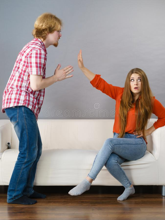 Man begging for forgiveness his woman. Man begging women who is sitting on sofa for forgiveness. Couple after fight or argue. Female showing speak to hand stock image