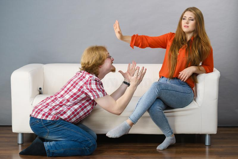 Man begging for forgiveness his woman. Man begging women who is sitting on sofa for forgiveness. Couple after fight or argue. Female showing speak to hand royalty free stock photography