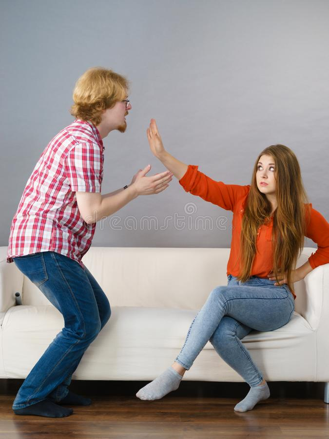 Man begging for forgiveness his woman. Man begging women who is sitting on sofa for forgiveness. Couple after fight or argue. Female showing speak to hand royalty free stock photos