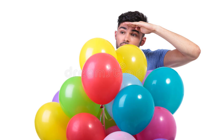 Man behind a bunch of baloons is looking away. Casual man behind a bunch of baloons is looking away to his side on white background stock photography