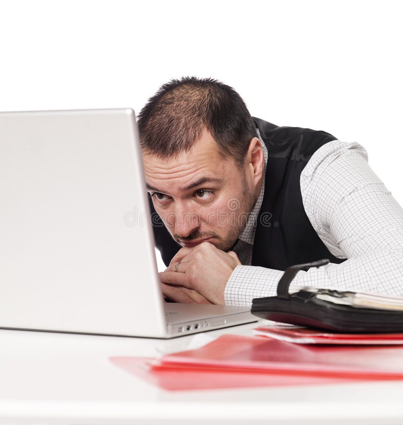 Man behind an office desk. Studying a laptop stock photo