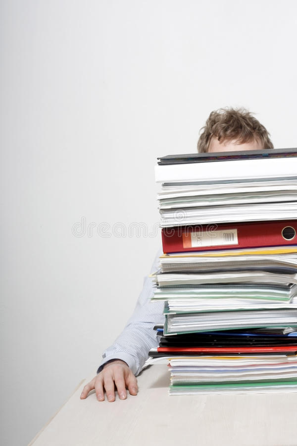 Man behind paperwork. Man sitting at a table, hidden behind a large stack of paperwork and files except for his right arm and hand, and his head from the royalty free stock images