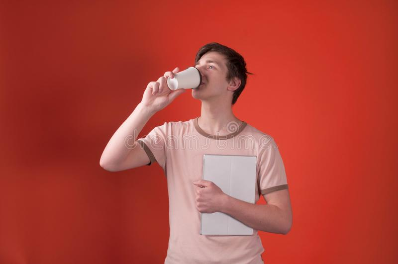 Man in beige t shirt standing with digital tablet, looking away and drinking coffee with paper cup stock image