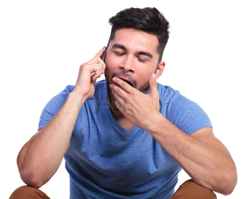 Man is being bored by the phone conversation. Seated casual man is being bored by the phone conversation stock photography