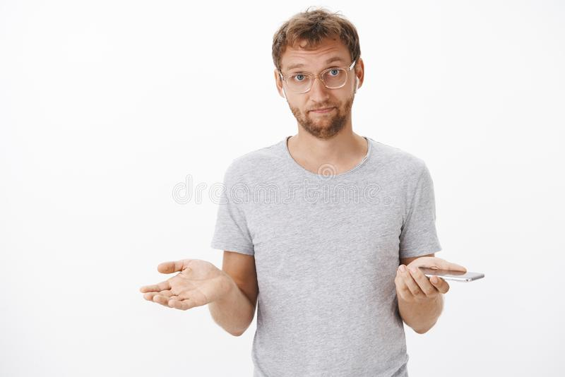 Man being bothered, can you see I listen music. Irritated handsome guy with brislte in glasses shrugging with spread. Hands in clueless gesture listening song royalty free stock images