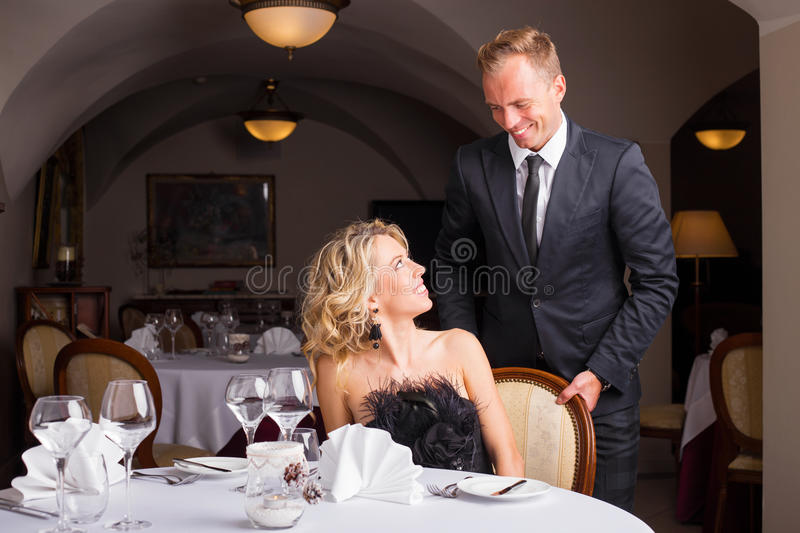 Man being a gentleman and helping woman with her chair stock photos
