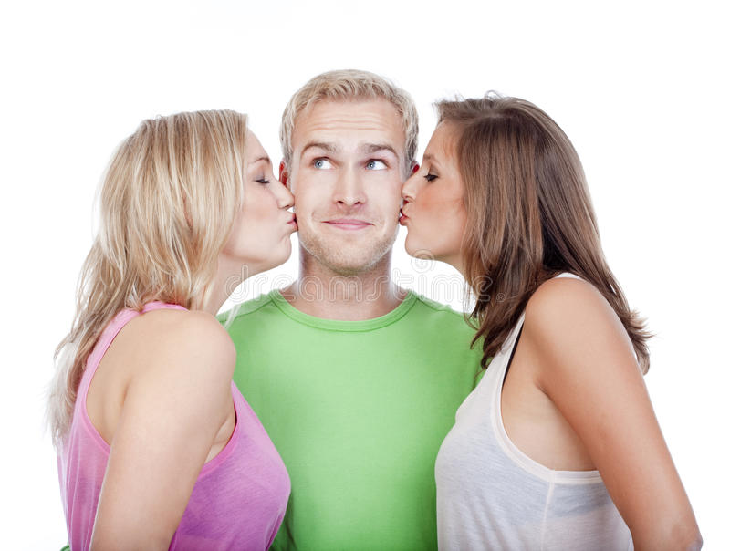 Man being kissed by two girls royalty free stock image