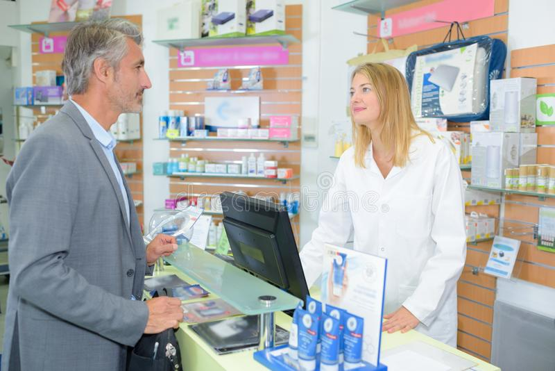 Man being served in pharmacy stock images
