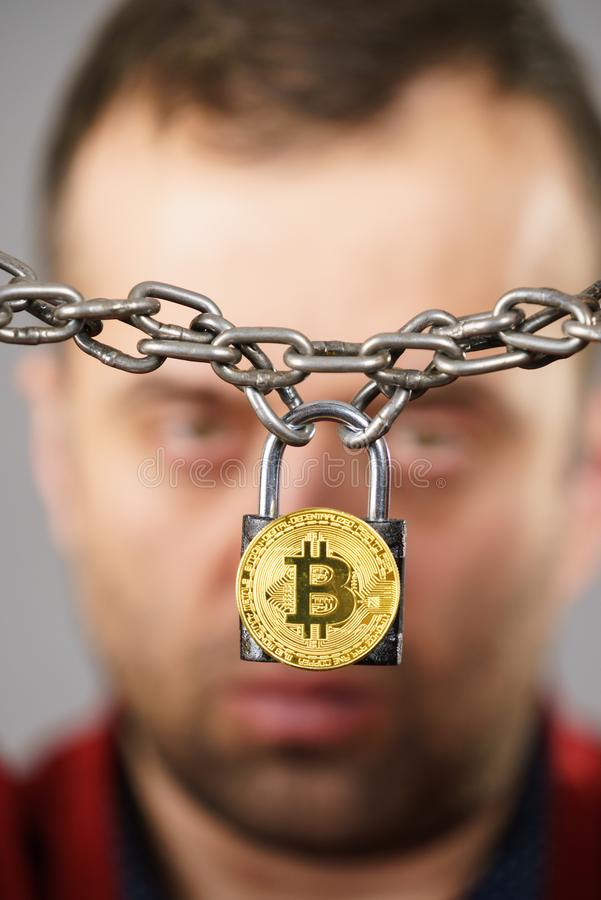 Man being tied up in block chain. Man having problems with crypto currency. Adult guy being tied up with block chain bitcoin stock image