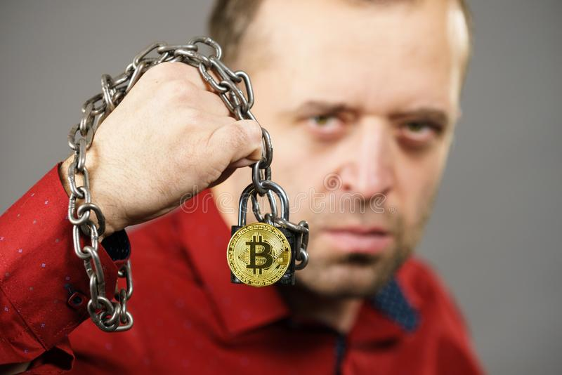 Man being tied up in block chain. Man having problems with crypto currency. Adult guy being tied up with block chain bitcoin royalty free stock image