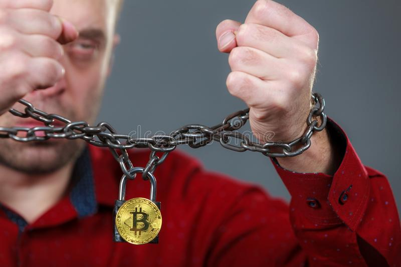 Man being tied up in block chain. Man having problems with crypto currency. Adult guy being tied up with block chain bitcoin stock photos