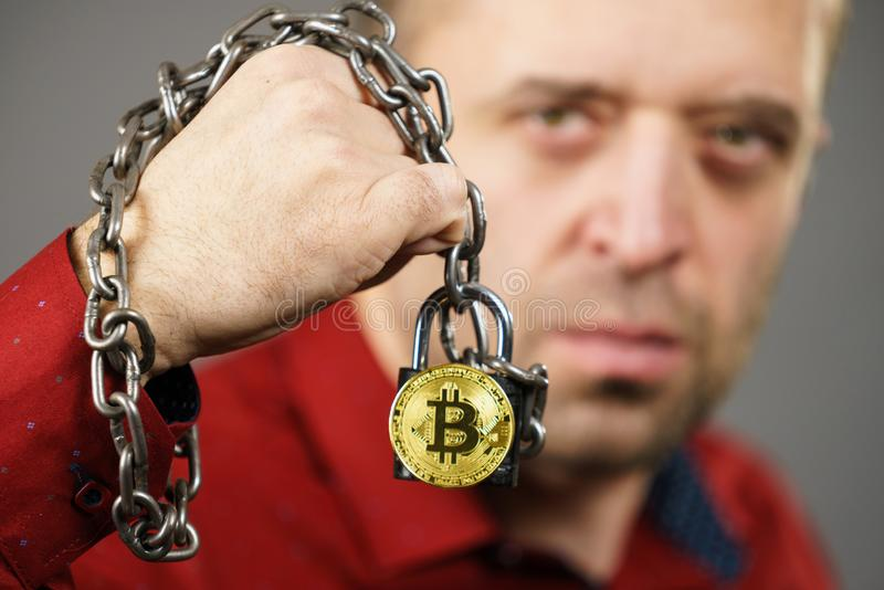 Man being tied up in block chain. Man having problems with crypto currency. Adult guy being tied up with block chain bitcoin stock images