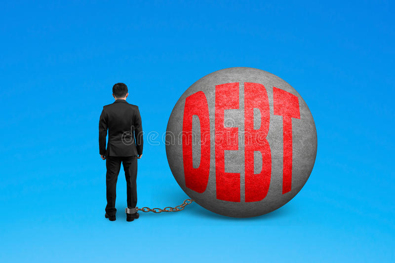 Man being trapped with debt ball. Isolated on blue royalty free stock images