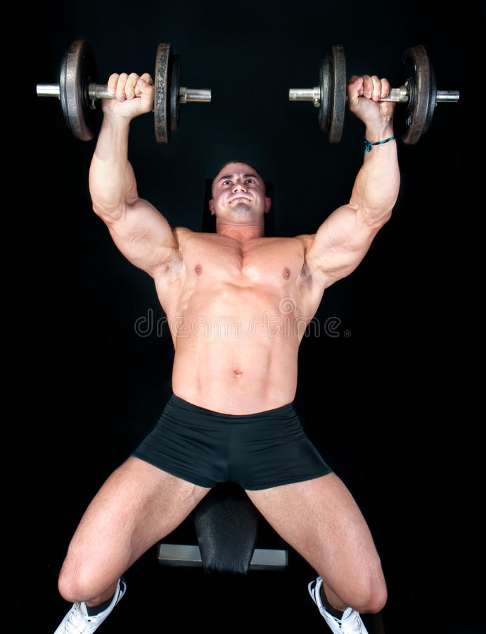 Man on bench with a bar weights in hands training stock photography