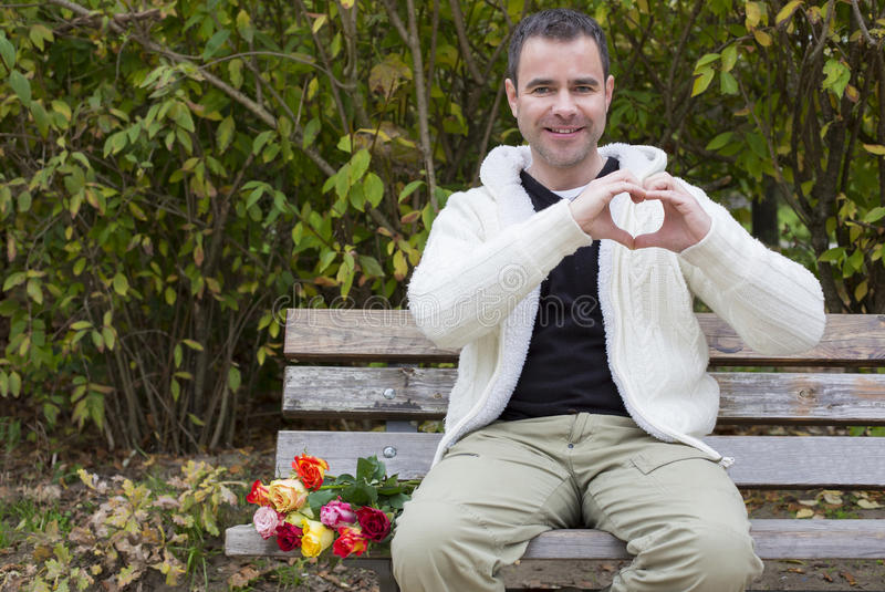 Man on bench shaping heart with his hands. Handsome man sitting outside with flowers on a bench and shaping a heart with his hands royalty free stock photo