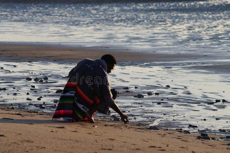 A man on bended knees at the beach stock images
