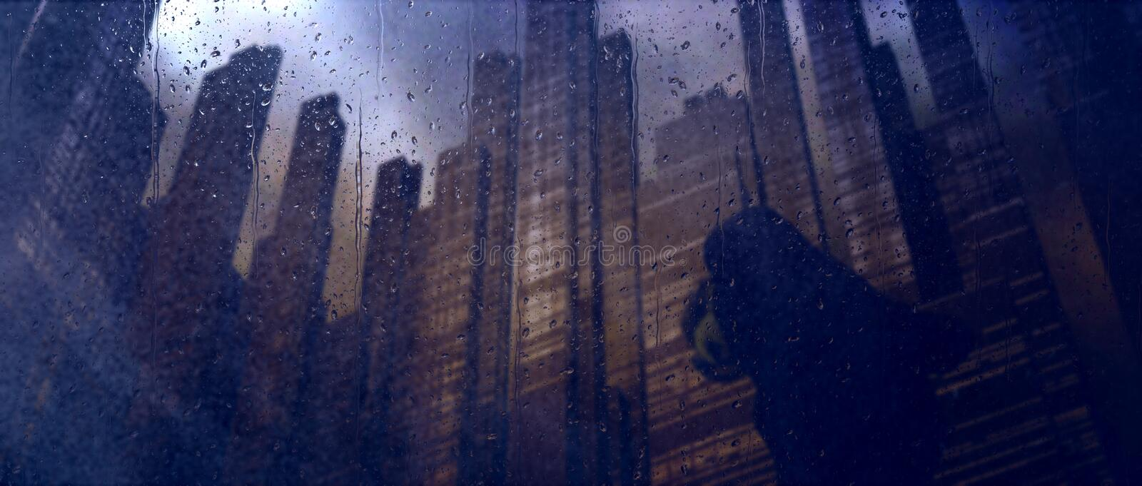 Dystopian dark city rain. Man bent over in rain under tall buildings