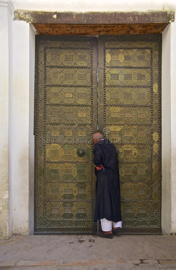Man in berber clothing knocking on the door stock photos