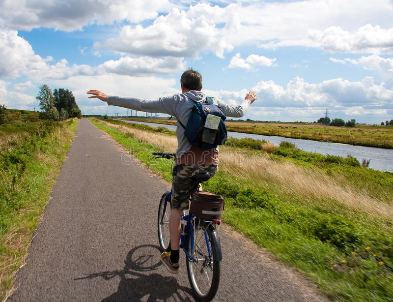 Man on bicycle having fun. Man having fun on a bike and riding without hands on a cycle path by a river in the English countryside royalty free stock image