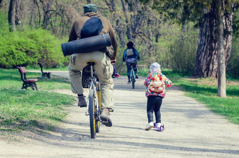 Belaya Tserkov, Ukraine - April 21, 2019: A man on a bicycle and a little girl on a scooter ride in the spring park.  stock photos