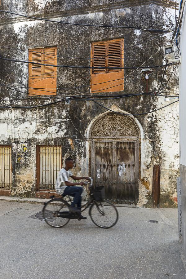 Man on a bicycle in the stone town streets and alley-ways. Urban and city life with the movement of a man on a bicycle in the rustic streets and alley-ways of royalty free stock photo