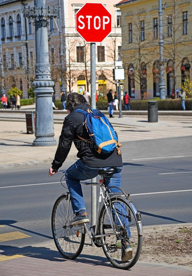 Man with bicycle at the stop sign in the city royalty free stock photography