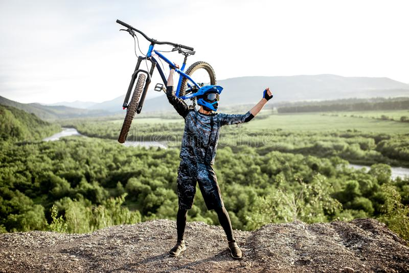 Man with bicycle on the top of the mountain royalty free stock photo