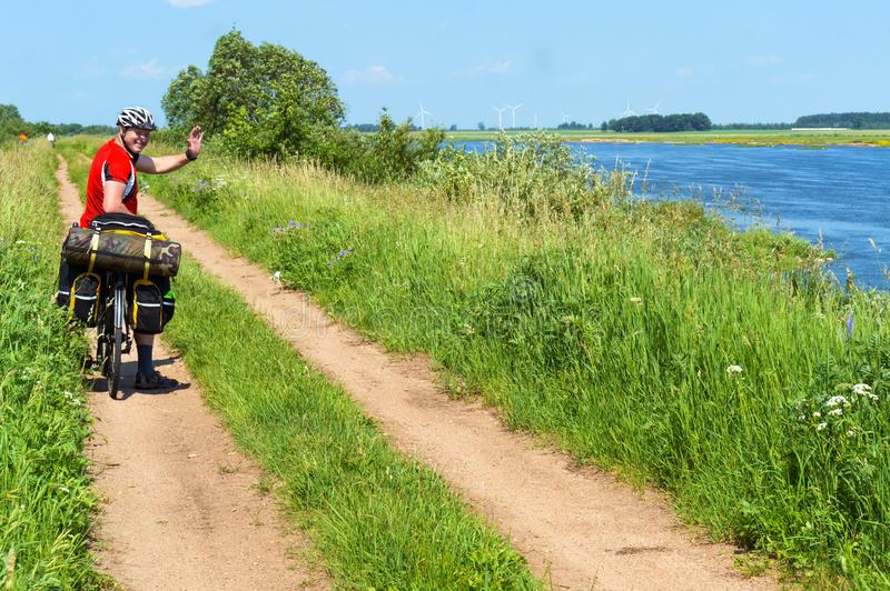 A man on a Bicycle travels in the summer along the river, cyclist with bags on a Bicycle royalty free stock photo