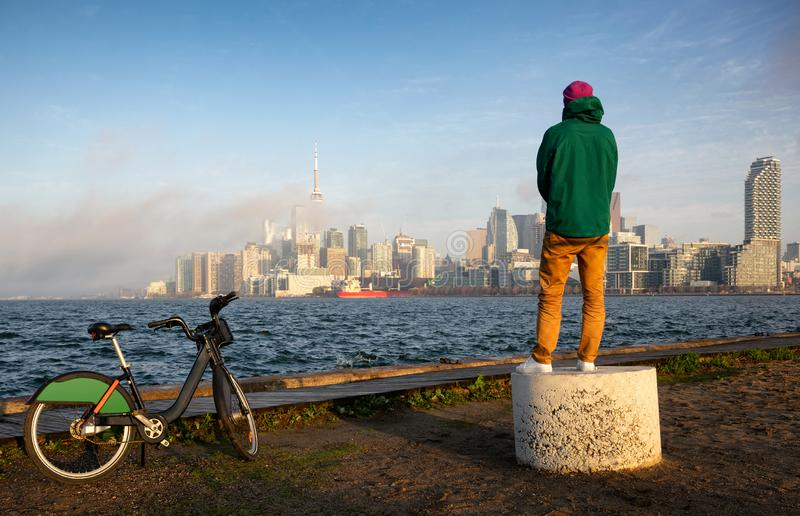 Man with bicycle watching sunset over lake Ontario Waterfront and Toronto downtown panorama stock photography