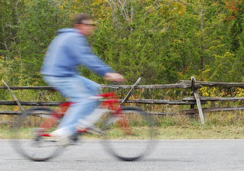 Man Bicycling On Country Road royalty free stock images