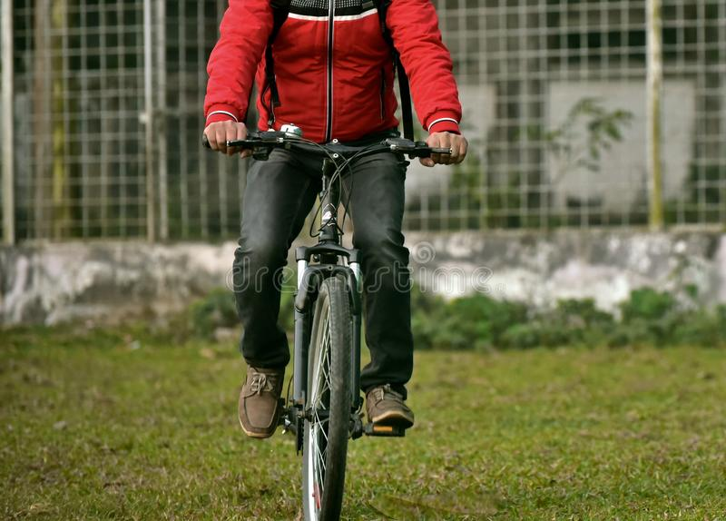 Man is bicycling wearing a red jacket stock photograph. An adult man is bicycling on a green ground surface isolated stock photograph stock images