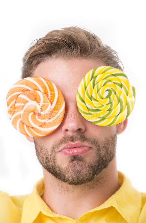 Man with big lollipops with hypnotizing pattern on eyes as eyeglasses. Hypnotized concept. Guy on calm face with giant royalty free stock photography
