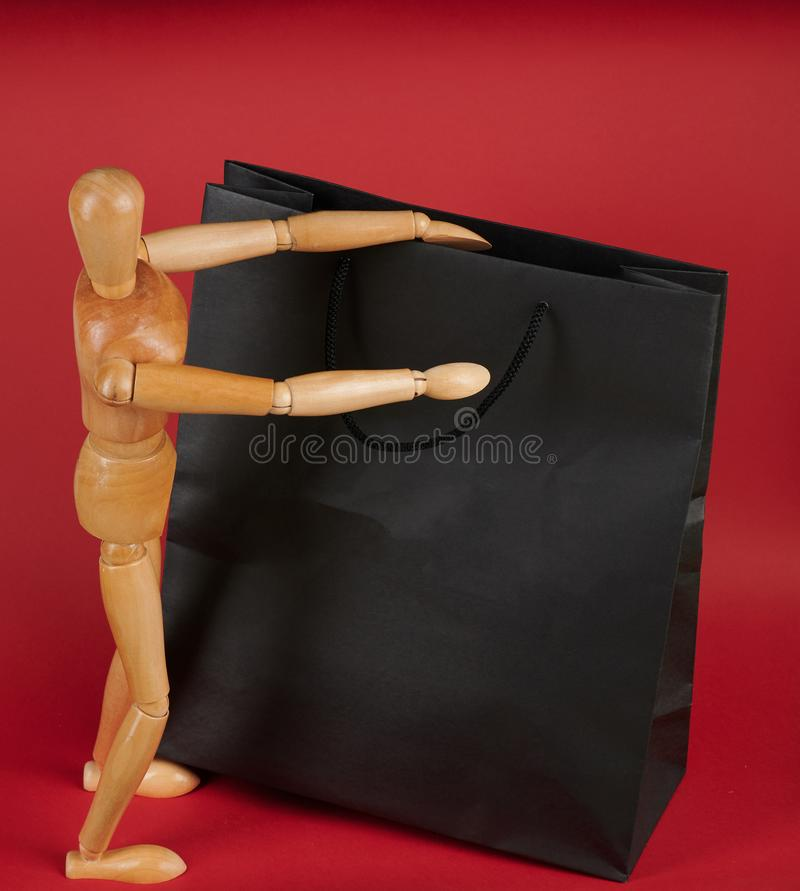 Man with big shopping bag. Wooden doll opening black paper bag royalty free stock photos
