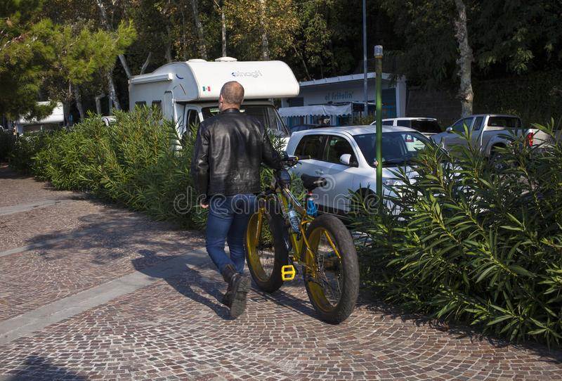 Man with big tire bike. TRIESTE, ITALY - OCTOBER, 2018: Man walking holding the big tire bike on October 14, 2018 royalty free stock photo