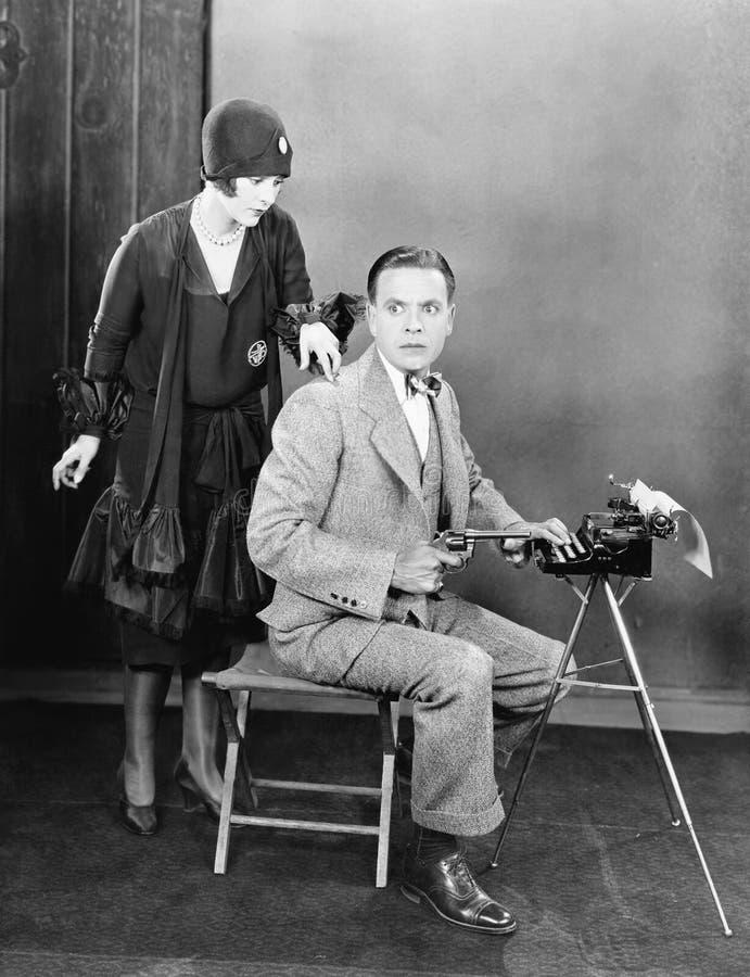Man bij een schrijfmachine een kanon en een vrouw die onttrekkend op zijn schouder houden (Alle afgeschilderde personen leven nie stock afbeelding