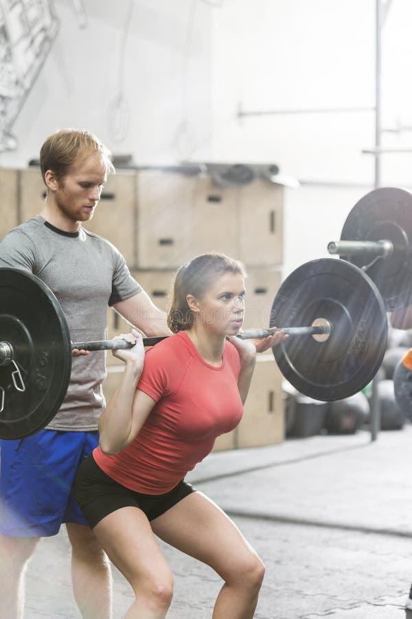 Man bijwonende vrouw in het opheffen barbell in crossfitgymnastiek stock foto