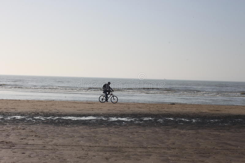 Man on bike on beach royalty free stock images