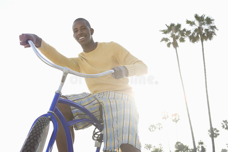 Man With Bike On Beach. Low angle view of a smiling man with bike on beach stock image