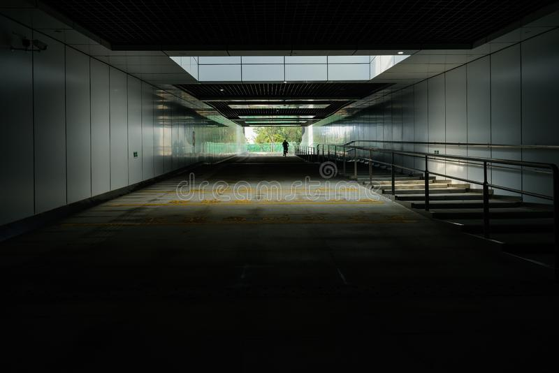 Man on bike at entrance of underground road tunnel with fenced p stock images
