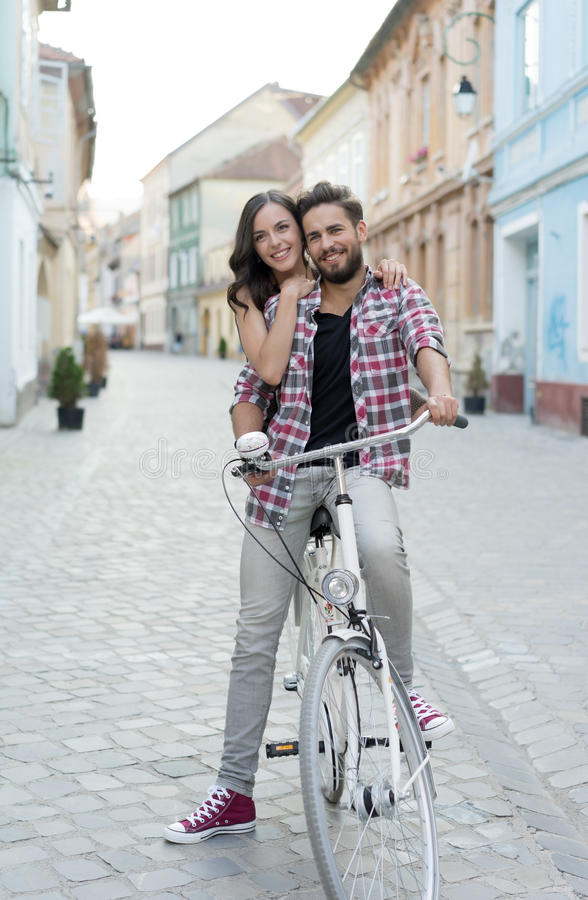 Man on a bike with his girlfriend behind. A handsome men on bike with his right leg down, stone street, girl's smiling, hugging male's shoulders royalty free stock image