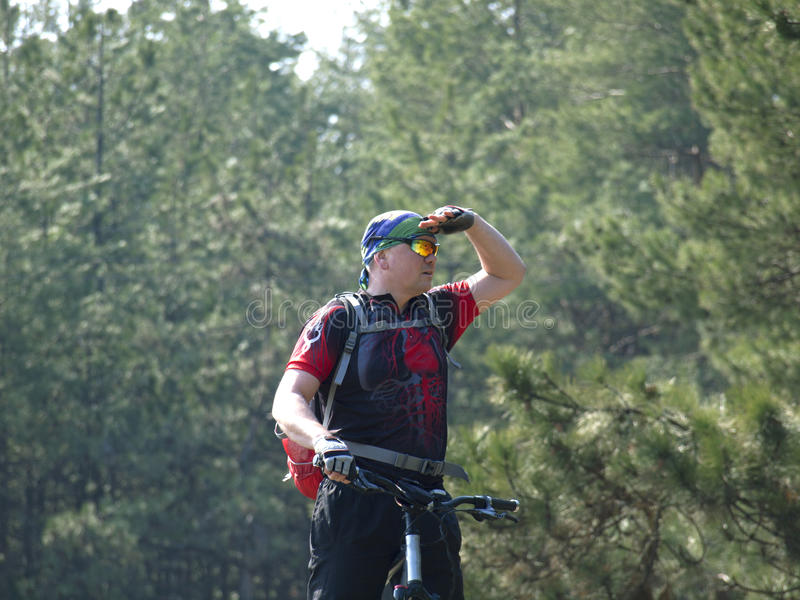 The man with the bike looks into the distance. The man with the bike in the woods looking into the distance royalty free stock photos