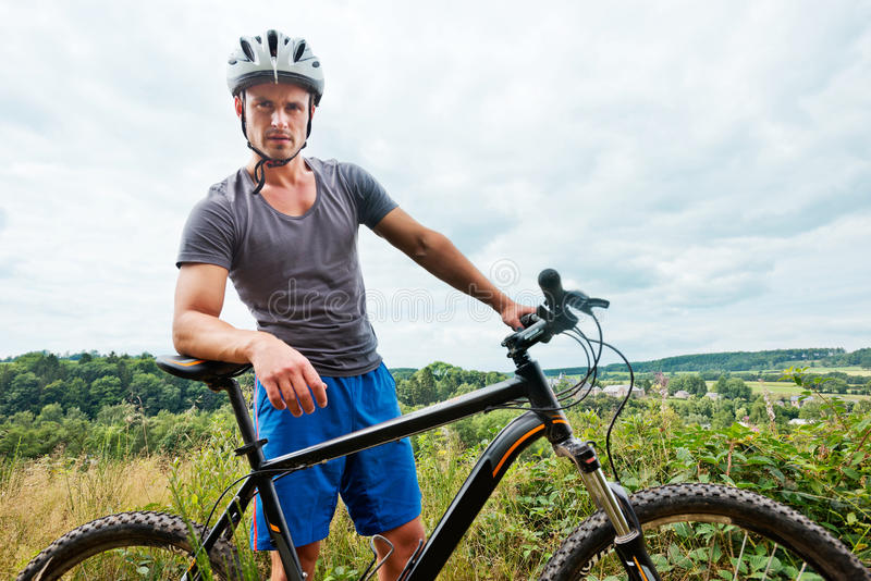 Man on bike. Portrait of a young man with a mountain bike in grassy landscape royalty free stock photography