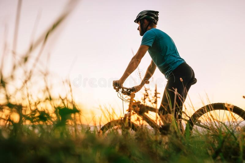 Man biker man meets a sunset in top of hill over the city. Active sport people concept image stock image