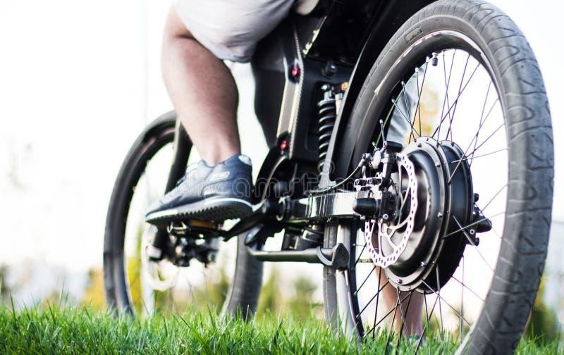 Man biker sitting on electric bike. Ebike bicycle environmentally friendly eco e-mountainbike transport. Healthy lifestyle royalty free stock photo