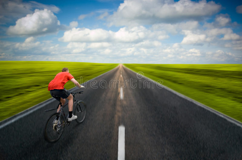 Man Biking On Road Stock Photo
