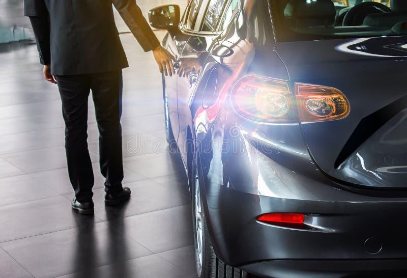Man bilen för den öppna dörren för affärssalemanen på gatan royaltyfria foton