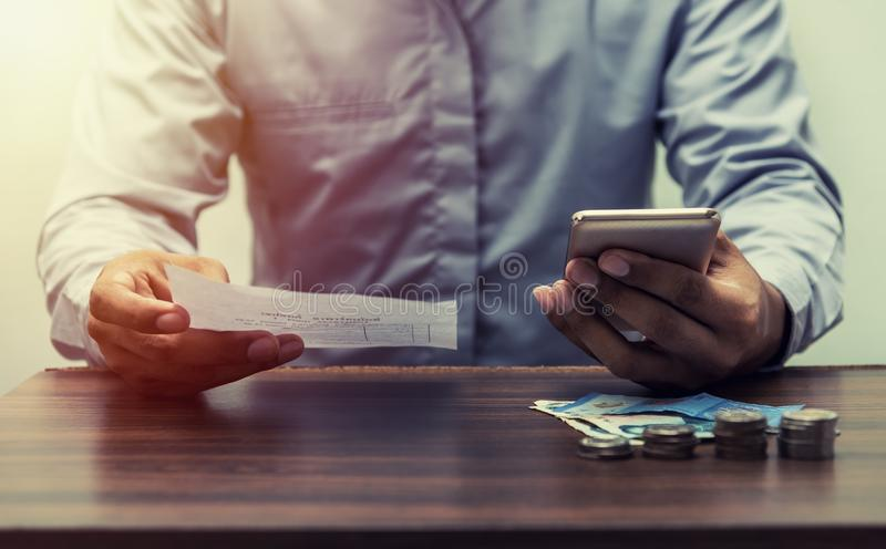 Save money save power and energy concept. Man with bill and mobile phone, smart phone, cellphone, laptop and stack of coin on business office table vintage style stock photography